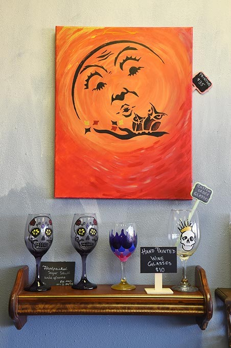 A painting overlooks hand painted wine glasses, at On the Edge with Skulls & Stones, at On the Edge with Skulls & Stones, in their new location in west OKC, 11-11-15. - MARK HANCOCK
