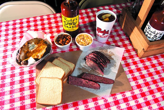 Spread of Rudy's Country Store and Bar-B-Q goodies includes baked potato, beans, cream corn, and Brisket, and of course Rudy's Sissy Sause.  mh