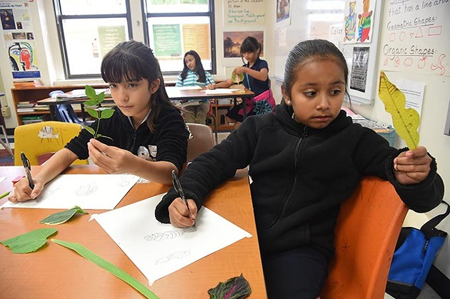 Left to right, Jackie Carrera and Emili Carrion, both 4th graders at Lee Elementary School in OKC, study their own leaves and transfer what they see to the paper as they participate in an after school art project at the Southside OKC School, 9-14-15. - MARK HANCOCK