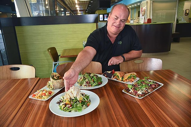 Owner Scooter Aselton with new and seasonal menu Items, from left, Southwest Spicy Wrap, Lemon Lychee Chicken Salad, the seasonal Summer Berry Salad, Sriracha Chicken Sandwich, and one of his favorites, the new Plaza Skinny Flatbread, at the Downtown OKC Coolgreens, 9-11-15. - MARK HANCOCK