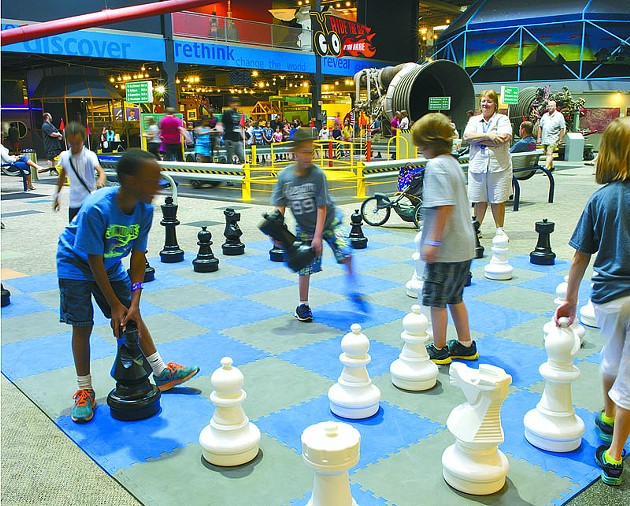 Kids enjoy playing chess with oversized pieces at Science Museum Oklahoma.Photo/Shannon Cornman - SHANNON CORNMAN