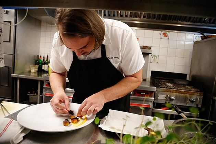 David Henry carefully plates a dish at The Coach House. (Garett Fisbeck)