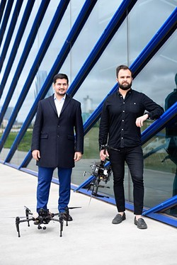 Ersin Demirci and Nick Brown pose for a photo with drones at the Boathouse District, Monday, April 11, 2016. - GARETT FISBECK