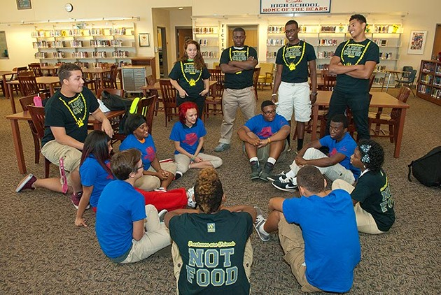 John Marshall High School Link Crew members with some of the freshmans they partner with, (blue shirts), in the library at the school showing how they first got together for orientation.  mh
