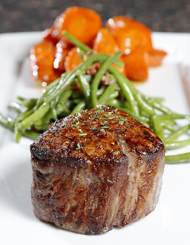 10 oz. Prime Filet with bacon green beans and glazed carrots at Ranch Steakhouse in Oklahoma City, Tuesday, April 14, 2015. - GARETT FISBECK