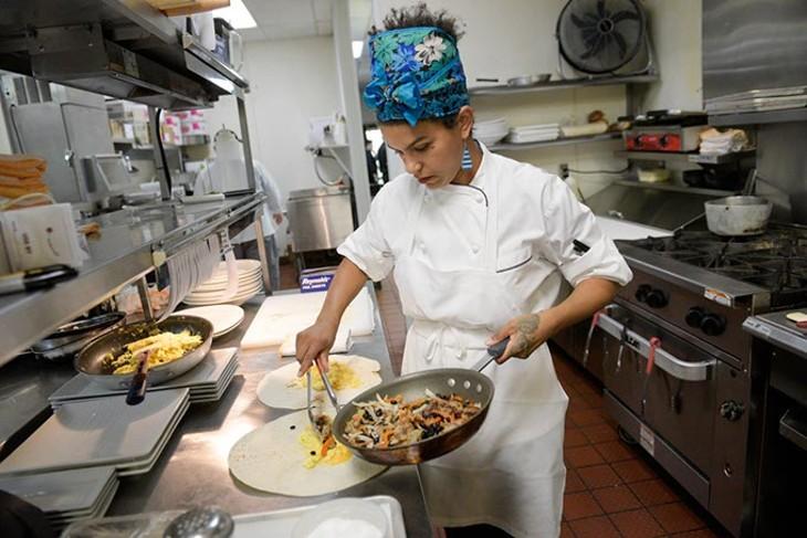 The Lobby Cafe & Bar breakfast chef Angela Renee Chase prepares sausage and egg breakfast burritos.   Photo Garett Fisbeck