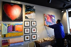 Brent Learned hands art for the Studio Gallery Spring Art Show, Tuesday, April 5, 2016. - GARETT FISBECK