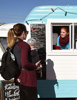 Customers Molly, left, and Samantha Cooper, order some hot chocolate at the Katiebut's camper, from Autumn Urton, left, and Jen Bellah, at the Holiday Pop-Up Shops in Midtown, 12-18-15, Oklahoma City. - MARK HANCOCK