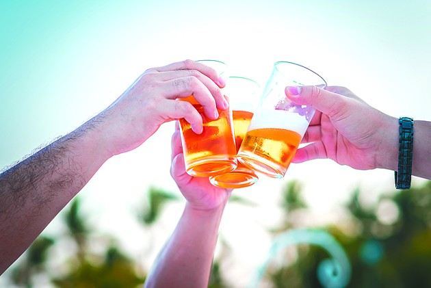 Hand holding glasses of beer clinking together at outdoor - BIGSTOCK