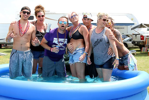 A group of campers from Oklahoma and Kansas pose in a blow-up pool in between their campsites at Rocklahoma in Pryor, Okla. on Saturday, May 27, 2017. (Cara Johnson).