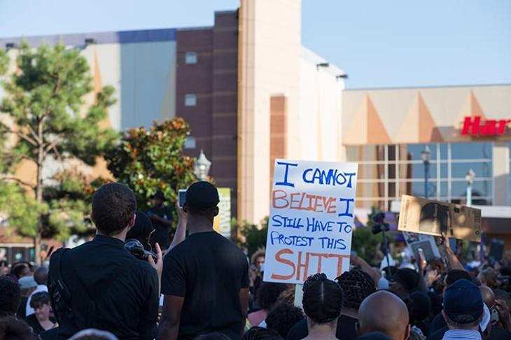 Protestors hold up signs at the Black Lives Matter protest on Sunday, July 10, 2016. - EMMY VERDIN