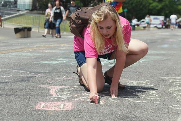 """Planned Parenthood volunteer Bailey Ashbaker writes """"I stand with Planned Parenthood"""" in chalk on 39th St. on Saturday, June 24, 2017. (Cara Johnson)."""