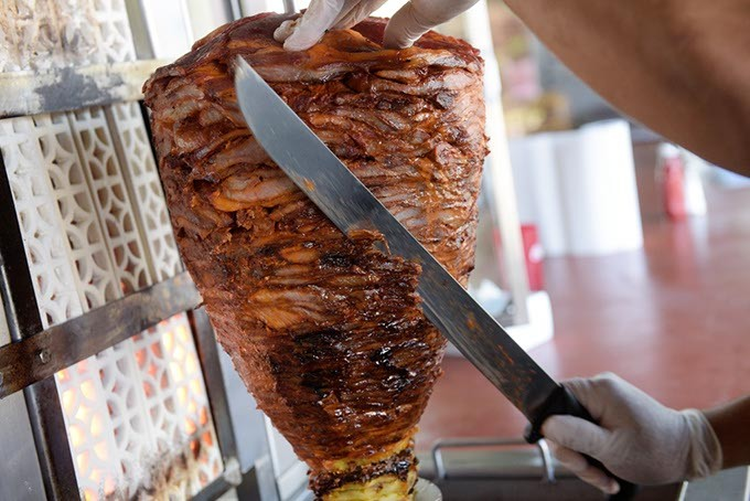 El Fogoncito partner and head cook Abisaid Samaniego cuts a trompo of pork. | Photo Garett Fisbeck