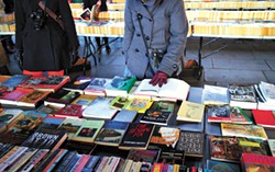 London, England - January 24, 2015: People browsing the books for sale at the Southbank Centre Book Market in London, England. Located beneath the Waterloo Bridge the market is open all year round. - BIGSTOCK