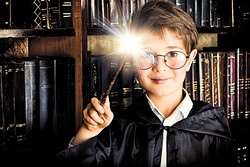 A boy stands with magic wand in the library by the bookshelves with many old books. Fairy tales. Vintage style. - BIGSTOCK