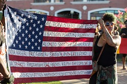 Marchers display a flag with the names of blacks killed by police during a Black Lives Matter rally and march July 10 in Bricktown. (Emmy Verdin)