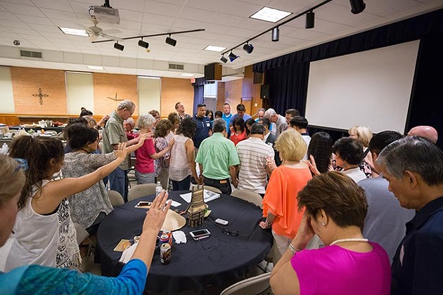 Reunion members say a prayer at the 23 reunion.  Missionaries, Gisela Huyssen and her husband Ulrich Huyssen adopted 23 Vietnamese children to American families at the end of the Vietnam war on Saturday, July 2, 2016 in Oklahoma City. - EMMY VERDIN