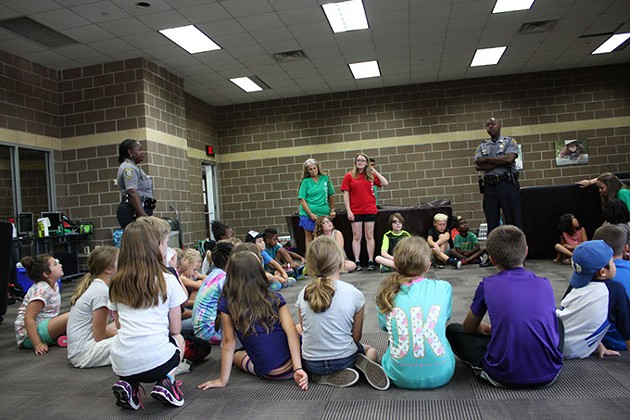 Sgt. Sherrica Buckingham left - and MSgt. Justin Echols listen as summer day - campers ask about the role of officers during - camp at Earlywine Park YMCA. | Photo Laura Eastes