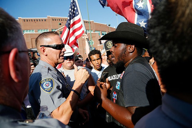 An Oklahoma City police officer talks with a counter protester during a Black Lives Matter demonstration in Oklahoma City, Sunday, July 10, 2016. - GARETT FISBECK