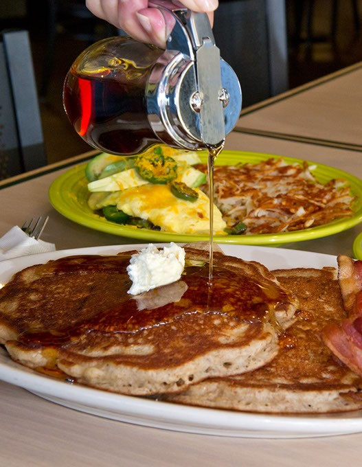 Multi-grain pancakes with chopped nuts cooked into the batter. Background, 3 egg omelet surrounded with jalapeno and cheddar, and added avacado on top. Biscuit and gravy on the side.Photo/Shannon Cornman - SHANNON CORNMAN