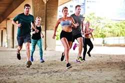 Determined group of young people running together in city. Running club members training together. - BIGSTOCK