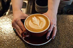 A fresh latte made by barista Tori Goben, at Coffee Slingers Roasters.  mh