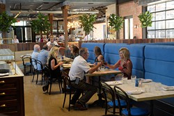 Patrons of The Jones Assembly toast during the dinner hour on July 13. The Jones Assembly is a restaurant, bar, live music and event venue that occupies a former warehouse in Oklahoma City's Film Row. (Garett Fisbeck)