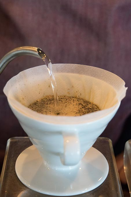 Barista pours hot water over coffee grounds at Elemental Coffee, Monday, May 15, 2017. - CARA JOHNSON