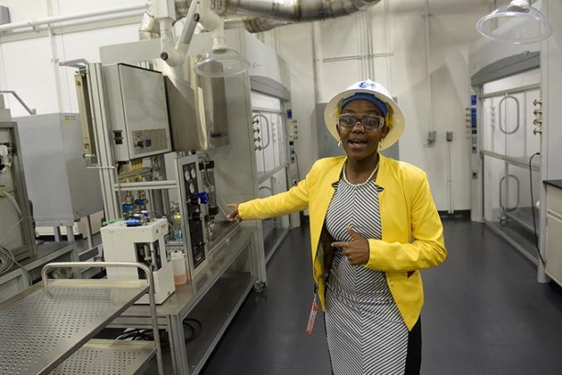 Lead lab engineer Paulina Mwangi talks - about the GE Global Research Oil and Gas - Technology Center laboratory during a recent tour. | Photo Garett Fisbeck