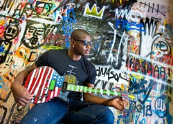 Desmond Mason with a newly painted American Flag guitar against an on going wall mural project in his Midtown studio, Oklahoma City.Photo/shannon Cornman - SHANNON CORNMAN