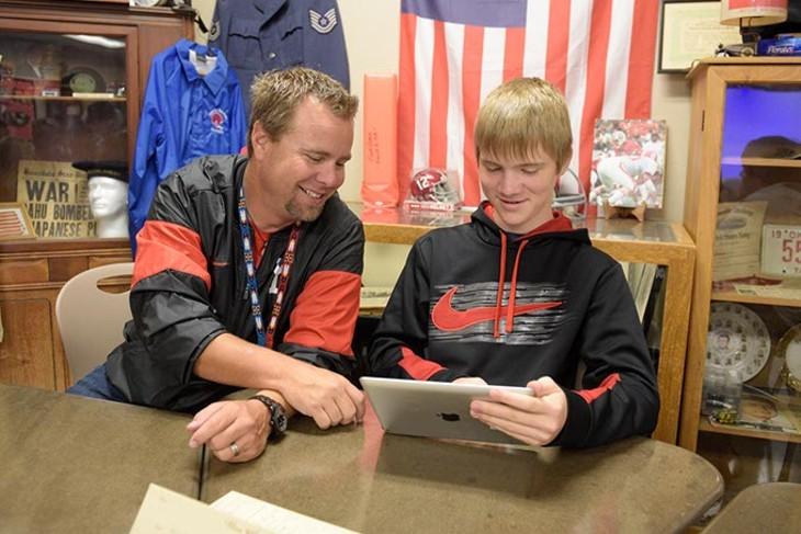 Rob Davis works with Erik Sproul in his classroom at Yukon High School. | Photo Garett Fisbeck