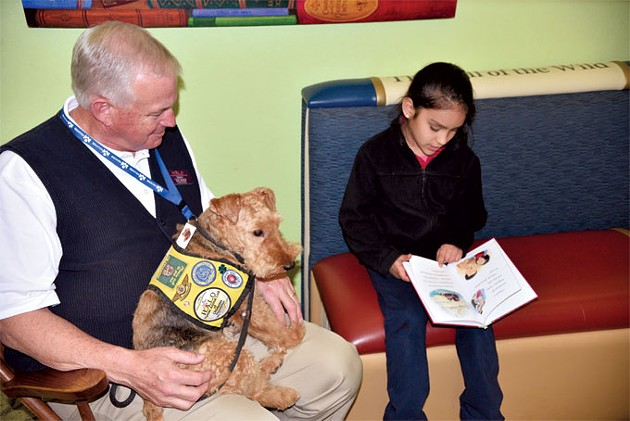 Brianna Montalvo reads to Charley the dog and her owner Jerry Nickell at The Village Library. | Photo Jacob Threadgill