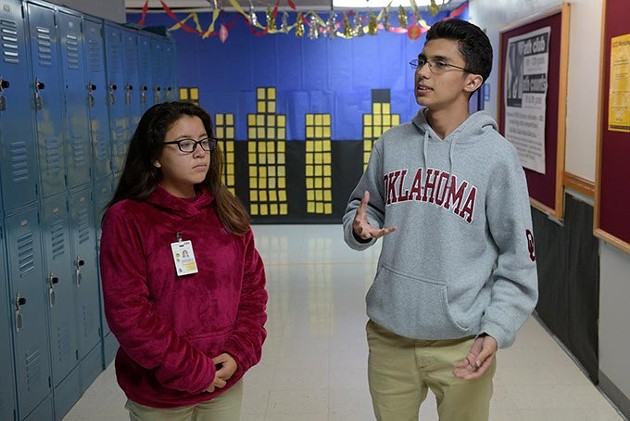 Senior Omar Camacho right explains how local college students visit Dove Science Academy OKC on Thursdays to mentor and help students like himself and Damaris Palma left with science homework. (Photo Garett Fisbeck)