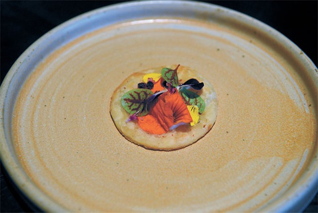 "A pork heart ""cracker"" topped with yogurt, red bell pepper and flower petals"