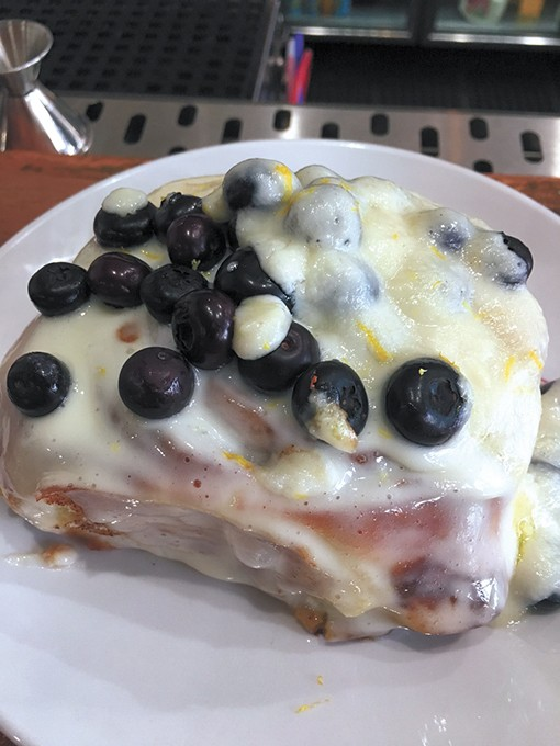 The citrus vanilla cinnamon roll with fresh  blueberries is one of three varieties only available  on the weekend. - JACOB THREADGILL