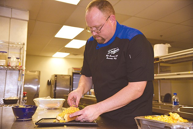 Executive chef Will Fenwick assembles a macaroni and cheese hot dog inside a kitchen at Chickasaw Bricktown Ballpark. - JACOB THREADGILL