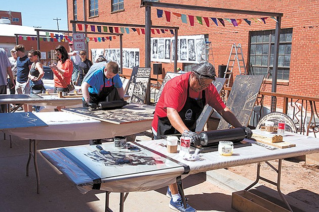 At [Artspace] at Untitled's Steamroller Print Fest, artists use a steamroller to press art onto various surfaces. - [ARTSPACE] AT UNTITLED / PROVIDED
