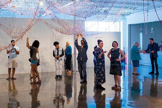 "Families add knots to ""A Thread X A Thread"" during the opening of Chiyoko Myose's Sojourning. - OKLAHOMA CONTEMPORARY ARTS CENTER / PROVIDED"