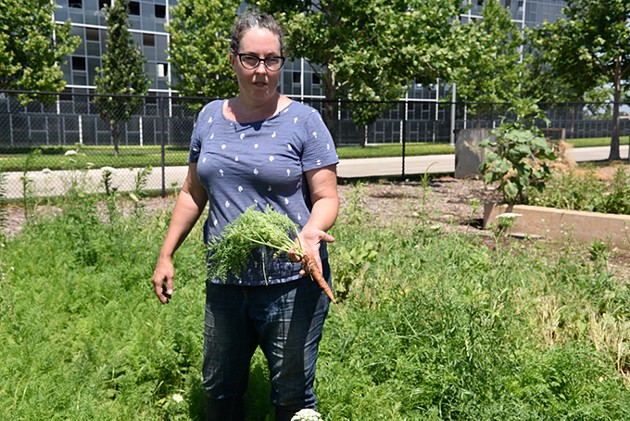 Gardener Jenn Mabry shows off a freshly harvested carrot from TLC Donation Garden. - JACOB THREADGILL