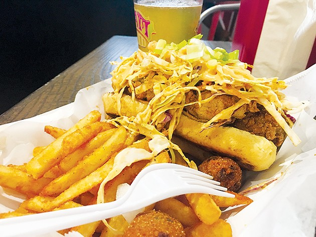 Fried oyster po'boy served with fries and hushpuppies - JACOB THREADGILL