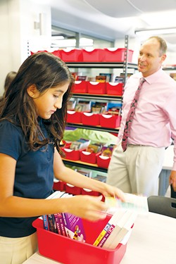 John Rex Charter School sixth-grader Adamari Hernandez looks through books stocked in her new classroom at Myriad Botanical Gardens as the school's director of secondary education Patrick Duffy meets with teachers and parents. - PROVIDED