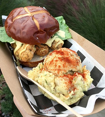 Seitan-based fried chicken is topped with honey mustard, pickles lettuce and served on a pretzel roll. - JACOB THREADGILL