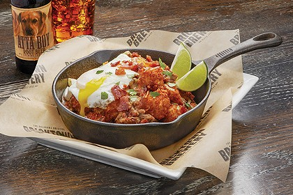 Green chili pork Totchos are topped with cheese, bacon and an egg. - PROVIDED