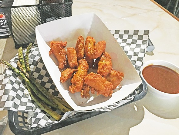 Chicken wings with a side of grilled asparagus - JACOB THREADGILL