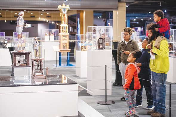 "Guests examine Jim Casey's ""Ezra the Chronicler"" and ""Henry the Contemplative Robot"" in Life Imagined: The Art and Science of Automata in Science Museum Oklahoma's smART Space galleries. - PHOTO SCIENCE MUSEUM OKLAHOMA / PROVIDED"