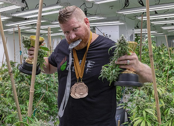 Tyler Doolittle poses with Fire Leaf's Cannabis Cup prizes. - PHILLIP DANNER