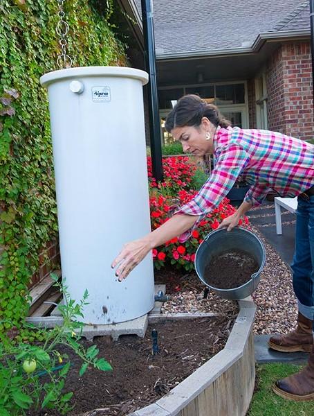 Jamie Csizmadia sprinkles some top soil over garden mulch next to a rain barrell at an Oklahoma City home. (Shannon Cornman)