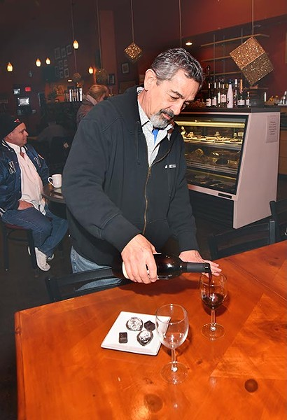 Michael Palermo, owner, pours Wine next to a selection of chocolate, the makings for a romantic get together, at Michaelangelo's Coffee and Wine in Norman, 1-21-16. - MARK HANCOCK