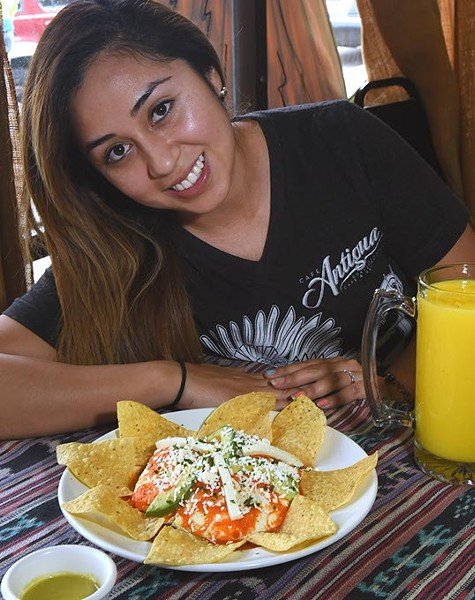 Cafe Antigua's Ana Sofia Del Cid, poses with vegitarian Huevos Motuleno double stack, with a fresh mango smoothy.  mh