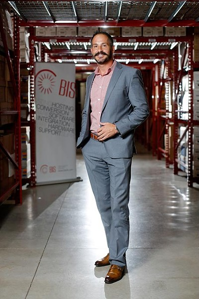 Danny Rotelli, owner of Business Imaging Solutions, poses for a photo in the warehouse of his business in Edmond, Tuesday, July 28, 2015. - GARETT FISBECK
